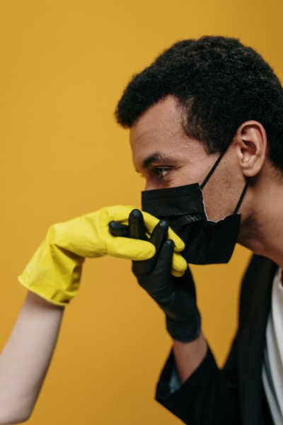 man in facemask kissing gloved hand